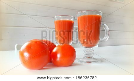 Still life on a white table with tomatoes and tomato juice in two glasses.