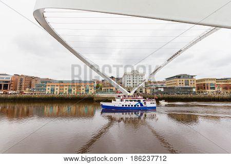 Boat Passing Under Tilted Millennium Bridge In Newcastle, Uk