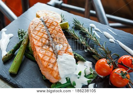 Delicious salmon steak with tomates over vintage background