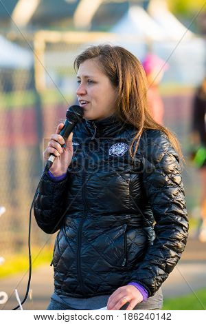 EUGENE, OR - MAY 7, 2017: Female reace announcer gives important info over the loud speaker prior to the start of the 2017 Eugene Marathon race held on the University of Oregon campus.