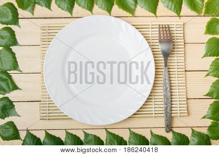 Empty plate on a bamboo mat with a fork view from top on a wooden background framed with leaves of a tree