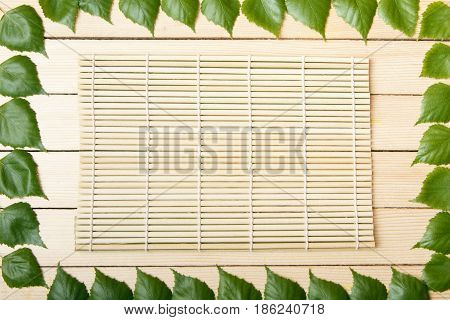 Bamboo mat top view on a wooden background framed with leaves of a tree