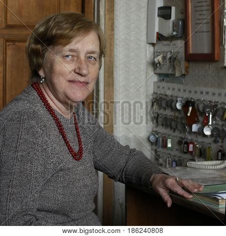 An elderly woman in gray sweater with beads looking directly into lens sits at the desk on her working place among keys magazines fire alarm instructions on wall