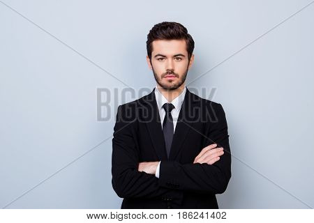 Portrait Of Handsome Strict Employer In Formal Clothes Standing With Crossed Hands Against Gray Back