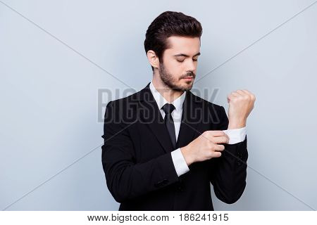 Portrait Of Stylish Handsome Man In Black Suit And White Shirt Buttoning Cufflinks