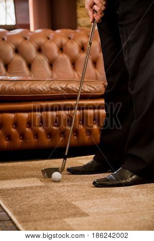 Man playing golf at home alone. Sport for recovering your nerves after hard working day or week. Golf at home concept.