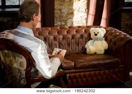 Psychiatrist man listening to his patient teddy bear and writing his psychological disease. Consultation at psychological office.