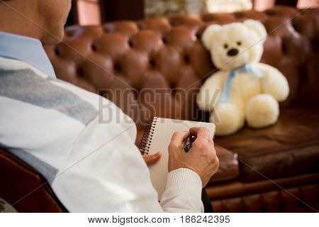 Psychology concept. Psychiatrist man listening to his patient teddy bear and writing his psychological disease. Consultation at psychological office.