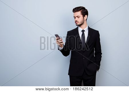 Young Concentrated Entrepreneur In Formal Suit Holding Hand In Pocket And Using Mobile Phone For Sen
