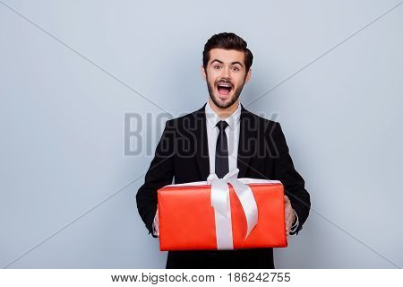 Excited And Impressed Man In Black Suit Holding Big Red Gift Box On Gray Background