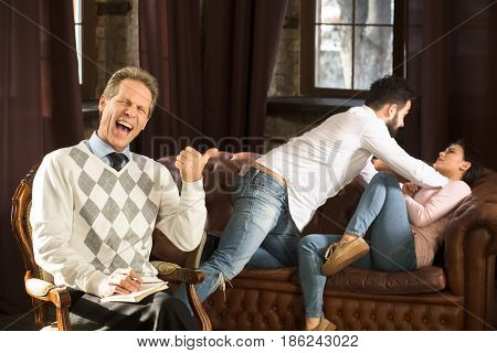 Couple man and woman having fight at psychologist's office. Psychology man happy laughing while they have battle on background.