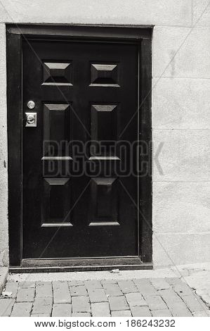 A black and white photo of a tall door.