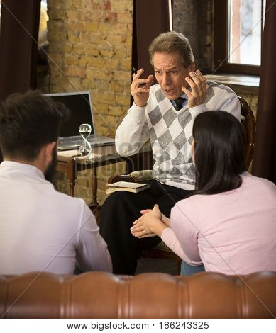 Psychology concept. Psychiatrist man working at psychologist's office. Middle aged man explaining existing situations in young family life.