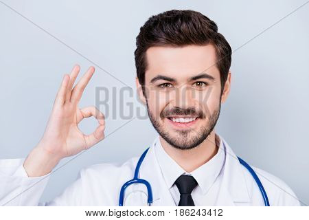 Close Up Photo Of Successful Experienced Smiling Doctor Showing Ok-sign