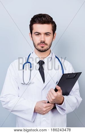 Vertical Photo Of Serious Confident Bearded Doctor With Stethoscope And Clipboard Ready For The Cons