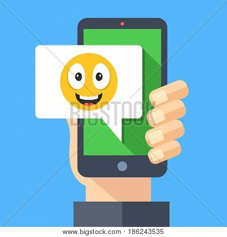 Hand holding smartphone with happy emoji message on screen. Happy emoticon icon. Social networking, instant messaging on mobile device, online chat concepts. Modern flat design vector illustration