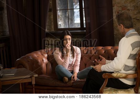 Young girl having professional psychological assistance at psychologist's office. Young lady telling about her problems with husband. Psychology concept. poster