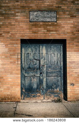 A blue broken textured door on yellow bricks.