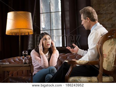 Psychology concept. Middle aged psychologist telling woman about her problems and how to solve them. Young woman listening to psychotherapist and thinking about her behaviour at psychologist's office.