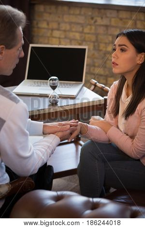 Psychology concept. Psychotherapist gives patient moral support. Young woman communicating with doctor at psychologist's office.