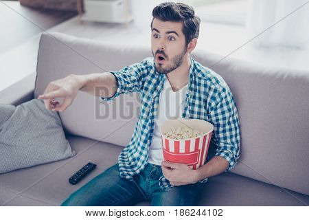 Portrait Of Impressed Man In Checkered Shirt Eating Popcorn While Watching Films On Tv At Home And H