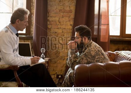 Military psychologist. Psychologist providing moral assistance to soldier who has been in hot spots. Military man communicating with psychologist.