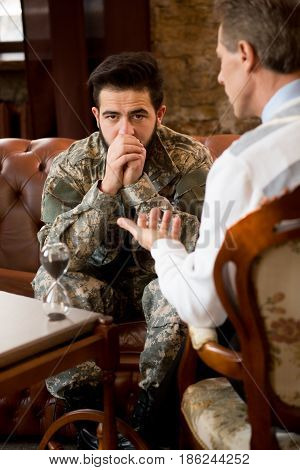 Military psychologist. Psychologist providing moral assistance to soldier who has been in hot spots. Handsome young military man communicating with psychologist at psychologist's office.