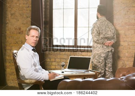Portrait of military psychologist communicating with military man and providing moral assistance to soldier who has been in hot spots. Military man staying near window at psychologist's office.