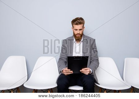 Young Stylish Man With Beard Is Preparing For The Interview. He Is In A Suit, Sitting In The Hall On