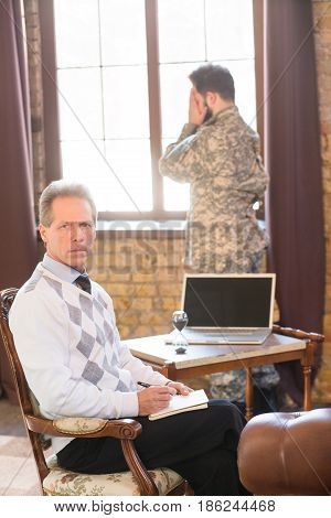 Military man staying near window at psychologist's office. Portrait of military psychologist communicating with military man and providing moral assistance to soldier who has been in hot spots.