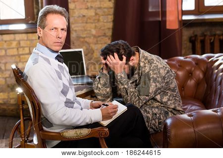 Communication of military psychologist and military man concerning existing problems in his life. Military man touching his head. Psychology concept.