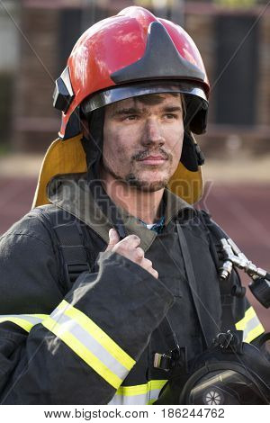 Close-up portrait of a young fireman on the background of a fire truck