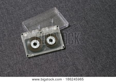 Old worn scratched audio cassette on a gray background with a box