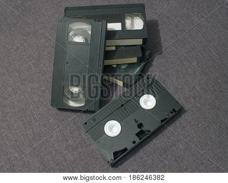 Five old vidio cassettes lie together gray background