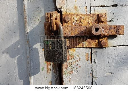 An old rusty metal latch with an iron lock on a wooden door painted with white paint an empty place for text.