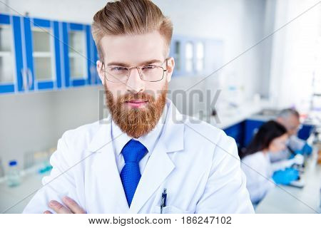 Close Up Portrait Of Young Successful Handsome Red  Bearded Researcher, Who Is  In The Lab, Wearing