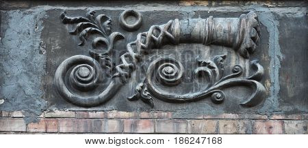 Embossed three-dimensional image on the wall of an old house above the brickwork: a long curved pipe in the form of a shell flowers and curls on a gray background.