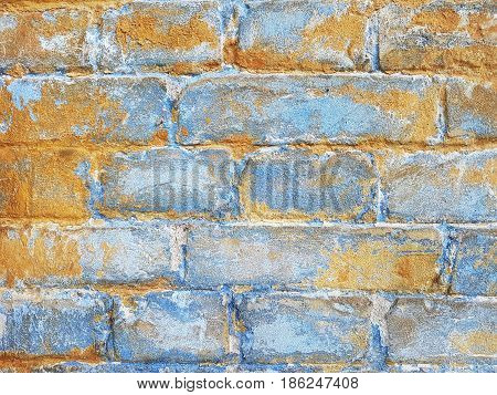 Fragment of the ancient brick wall of the last century cement masonry yellow and blue surface color.