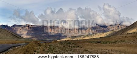 Morning on the Leh-Manal Highway: the asphalt road passes through the high desert in the background the mountains sunlit dawn and powerful cumulus clouds in the bright sky.