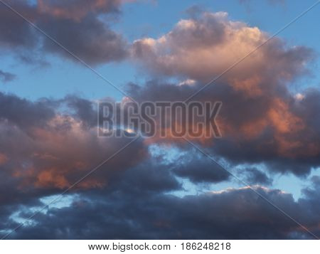 The sky before the storm: heavy rain clouds black and gray tinted in places in pink rays of the setting sun on a blue background.