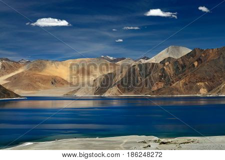 High mountains of Lake Pangong: dark blue water bright brown mountains and white cirrus clouds in the sky a summer trip through the Himalayas India.