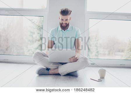 Cheerful Student Is Studying With His Laptop Sitting On The Floor At Home. He Feels Relaxed And Happ