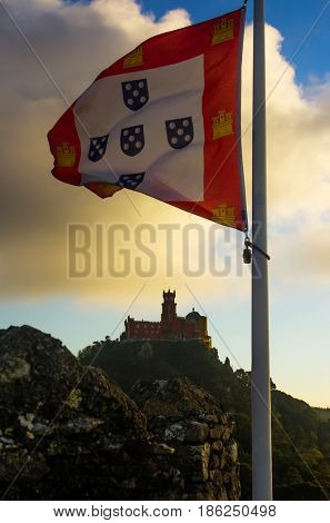 Pena Palace in Sintra, Portugal, and an ancient portuguese flag in the foreground