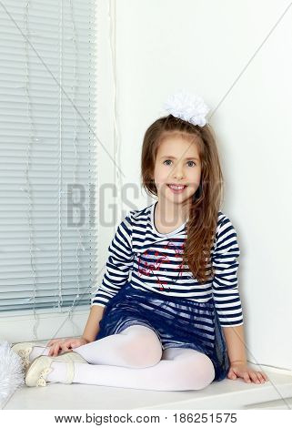 Little girl in blue striped dress and a white bow on her head.She sits at the window and looking straight to the camera.