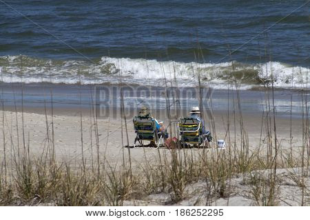 Carolina Beach, North Carolina, USA - April 11, 2017: A couple of older people covered up from the sun enjoy the sea from their beach chairs
