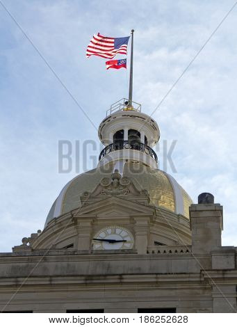 Savannah Georgia USA - January 20 2017: The golden clock tower at the top of the Savannah City Hall building with the American flag and the Georgia state flag flying from it on a sunny day