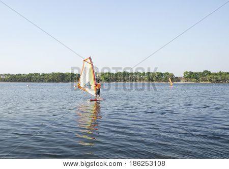 Man winsurfing on calm lake, recreational sporting activity.