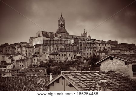Medieval town skyline view with Siena Cathedral and historic buildings in Italy at night