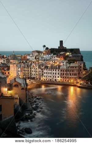 Vernazza at night with buildings on rocks over sea in Cinque Terre, Italy.