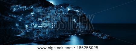 Manarola overlook Mediterranean Sea with buildings over cliff and moonrise in Cinque Terre at night panorama, Italy.